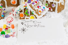 Letter to Santa. Closeup horizontal photo of letter to Santa with Gingerbread houses, surrounded by powdered snow in background Stock Image