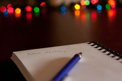 Letter to Santa. A Dear Santa Christmas letter started on a notepad with christmas lights in the background Royalty Free Stock Image