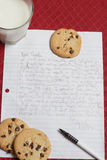 Letter to Santa. Vertical Image. Little kids Letter to Santa Clause asking for gifts. On a red table cloth with cookies and milk. Vertical Image Royalty Free Stock Photography
