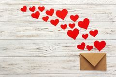 Letter to Valentine Day. Love letter envelope with red hearts on wooden background.  stock photos