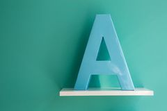 Letter A turquoise color on a white shelf Stock Image