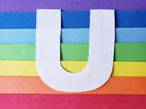 Letter U in white with background in rainbow colors. Backdrop for ads related to colors and lgbt community, graphic sign of a writing system with multicolor stock images