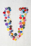 Letter V of the alphabet of buttons of various shapes and colors Royalty Free Stock Images