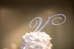 The Letter `V` Cake Topper. Made of diamond rhinestone with the main metal being silver. Sits on top of a light pink icing and cake topper stock photos