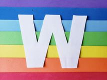 Letter W in white with background in rainbow colors. Backdrop for ads related to colors and lgbt community, graphic sign of a writing system with multicolor stock photo