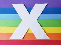 Letter X in white with background in rainbow colors. Backdrop for ads related to colors and lgbt community, graphic sign of a writing system with multicolor royalty free stock images