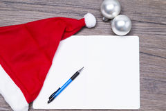 Letter of wishes. Blank christmas letter with red hat on a wooden table stock photo