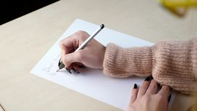 Letter and writing concept. Woman writing a letter with a pencil on a table at home stock video