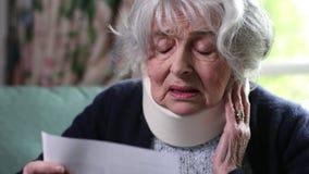 Lettera d'uso della lettura del collare del collo della donna senior stock footage