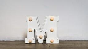 Lettera dell'alfabeto Luce notturna nella scuola materna La lettera bianca m. con la lampadina è sul pavimento immagini stock