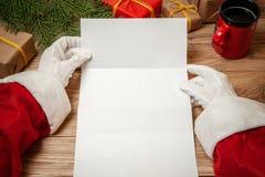 Lettera della tenuta di Santa Claus sulla tavola di legno con i contenitori di regalo e l'albero di Natale e sulla tazza di caffè fotografia stock libera da diritti