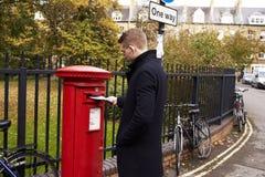 Lettera di invio dell'uomo in Postbox britannico rosso immagini stock libere da diritti