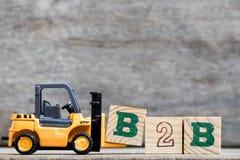 Lettera di plastica gialla B della tenuta del carrello elevatore per completare B2B immagine stock libera da diritti