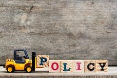 Lettera di plastica gialla P della tenuta del carrello elevatore per completare politica di parola Fotografie Stock Libere da Diritti
