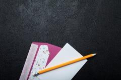Lettera e busta vuote, cartolina di carta su un fondo nero Copi lo spazio immagini stock libere da diritti