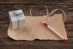 Lettera e scatola sulla tavola di legno per il giorno di biglietti di S. Valentino Immagini Stock