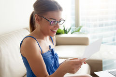 Lettera felice della lettura della donna sul sofà a casa Fotografia Stock Libera da Diritti