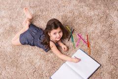 Lettera sveglia di scrittura della ragazza sul pavimento Immagini Stock