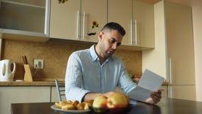 Lettera turbata della lettura del giovane con la fattura non pagata nella cucina a casa immagine stock libera da diritti