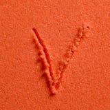Lettera V scritto sulla sabbia arancio fotografia stock