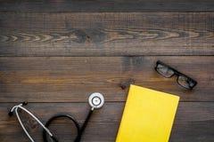 Letteratura medica Stetoscopio vicino al libro ed ai vetri sullo spazio di legno scuro di vista superiore del fondo per testo Fotografia Stock