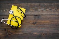 Letteratura medica Stetoscopio vicino al libro ed ai vetri sullo spazio di legno scuro di vista superiore del fondo per testo Immagini Stock Libere da Diritti