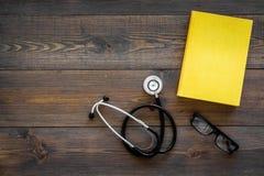 Letteratura medica Stetoscopio vicino al libro ed ai vetri sullo spazio di legno scuro di vista superiore del fondo per testo Fotografie Stock Libere da Diritti