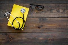 Letteratura medica Stetoscopio vicino al libro ed ai vetri sullo spazio di legno scuro di vista superiore del fondo per testo Immagine Stock