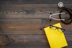 Letteratura medica Stetoscopio vicino al libro ed ai vetri sullo spazio di legno scuro di vista superiore del fondo per testo Fotografie Stock