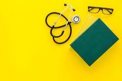 Letteratura medica Stetoscopio vicino al libro ed ai vetri sullo spazio giallo della copia di vista superiore del fondo Immagine Stock Libera da Diritti