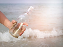 Letterbottom. Hand holding a bottle with a letter inserted inside by the sea Royalty Free Stock Photo