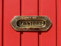 Letterbox. A brass letterbox on a red door Stock Image