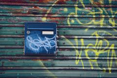 A letterbox on a textured graffiti wall. Underground and dirty background royalty free stock image