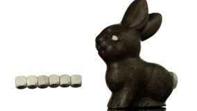 Lettere che spiegano pasqua che cade accanto al coniglietto del cioccolato video d archivio