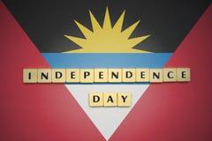 Lettere con la festa dell'indipendenza del testo sulla bandiera nazionale dell'Antigua e di Barbuda Fotografia Stock