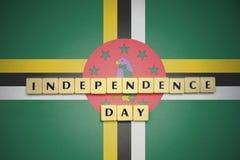 Lettere con la festa dell'indipendenza del testo sulla bandiera nazionale della Dominica Fotografia Stock Libera da Diritti