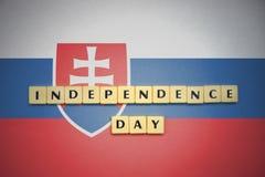 Lettere con la festa dell'indipendenza del testo sulla bandiera nazionale della Slovacchia Fotografia Stock