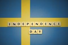 Lettere con la festa dell'indipendenza del testo sulla bandiera nazionale della svezia Fotografie Stock Libere da Diritti