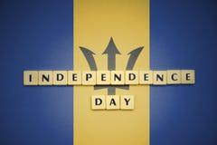 Lettere con la festa dell'indipendenza del testo sulla bandiera nazionale delle Barbados Fotografia Stock Libera da Diritti