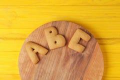 Lettere del biscotto sul bordo di legno Fotografie Stock