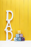 Lettere del testo del PAPÀ con i contenitori di regalo su fondo di legno giallo Immagini Stock Libere da Diritti