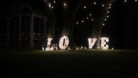 Lettere di legno con le luci di lampadina Parola - amore Parola illuminata AMORE sulla fase Amore di parola che consiste delle lu video d archivio