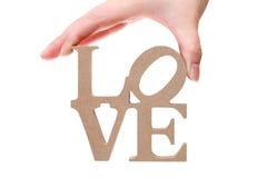 Lettere di legno del blocchetto della tenuta della mano, amore di parola Fotografie Stock