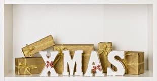 Lettere di legno di natale di bianco su un fondo bianco con il regalo imballato Immagine Stock