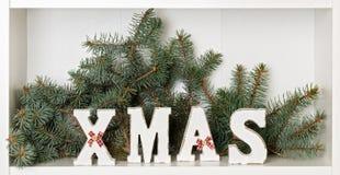 Lettere di legno di natale di bianco su un fondo bianco con il regalo imballato Fotografia Stock Libera da Diritti