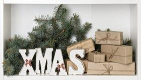 Lettere di legno di natale di bianco su un fondo bianco con il regalo imballato Fotografia Stock