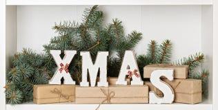 Lettere di legno di natale di bianco su un fondo bianco con il regalo imballato Immagine Stock Libera da Diritti