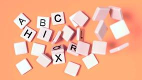 Lettere di plastica che rimbalzano e che mostrano alfabeto sulla superficie dell'arancia archivi video