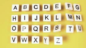 Lettere di plastica che rimbalzano e che mostrano alfabeto sulla superficie di giallo archivi video