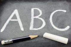 Lettere, gesso e matita di ABC sulla lavagna Immagini Stock